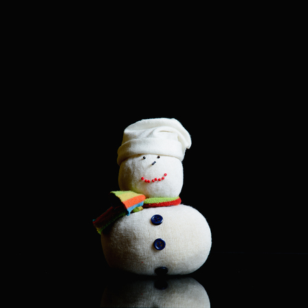 Snowman figure on a black background. He has a stocking cap, eyes, mouth and nose made with small beads, a shawl, buttons on a belly, and a red heart on his chests. Contrasty low key photograph.