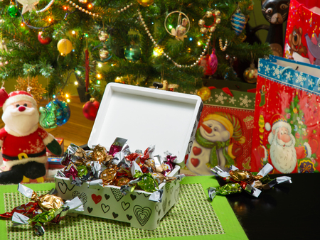 Decoupage box full of traditional Hungarian parlour candies. Beautifully decorated Christmas tree, gift bags under it, and a Santa Claus puppet are in a blurry background. Selective focus. Фото со стока