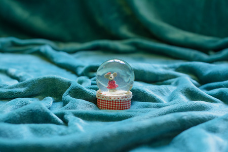 Vast area covered with beautiful cyan blanket drapes, and a crystal snowglobe with a mouse in it, in the center of the blanket. Selective focus. Imagens