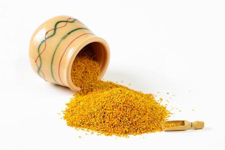 Heap of bee pollen granules, a wooden scoop and an overturned glazed clay pot full of pollen. Selective focus. Closeup.