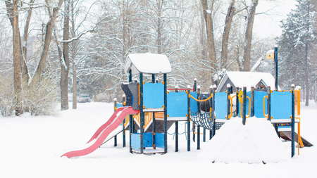 Children playground in a public park in winter. It is snowing. There are trees and naked tree branches covered with snow in the background.