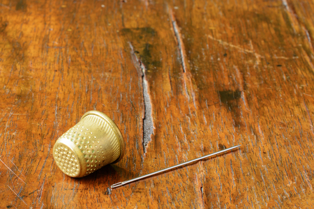 Thimble and a needle on an antique wood veneer full of cracks and scratches. Selective focus. Closeup.