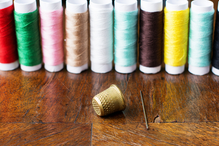 Thimble and a needle. Spools of thread in a blurry background.