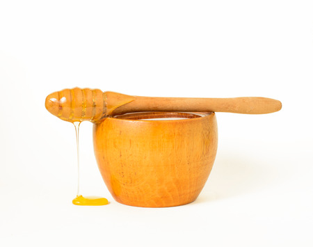 Honey in a wooden bowl and a honey dipper, a special kind of kitchen utensil used to collect honey from a vessel.
