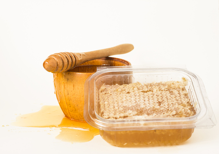 Cut honeycomb in a plastic container, honey in a wooden bowl and a wooden honey dipper.