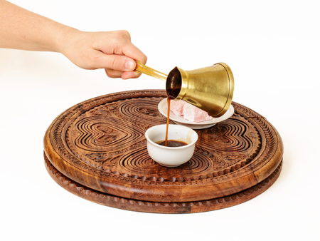 She is serving a black coffee from Turkish coffee pot  , and pouring it in Turkish coffee cup (a fildzan).