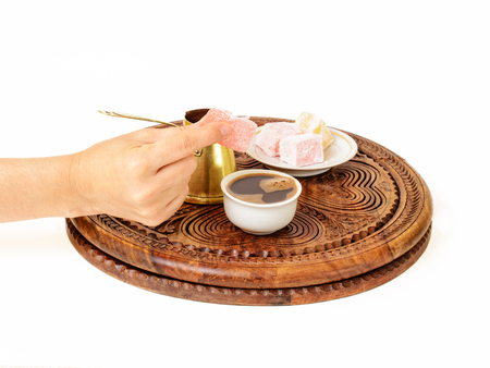 Turkish coffee is served in a traditional manner. A woman's hand is offering rahat lokum to you to fulfill your coffee drinking experience. Imagens