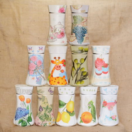 Colorful decoupaged jars arranged in a triangular manner. Decoupage has different decorative motifs. One of the jars has written on it word Flowers in French. Stock Photo
