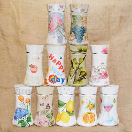 Jars decorated with decoupage technique arranged in a triangular manner. Decoupage has different decorative motifs. One of the jars has written on it word Flowers in French. Фото со стока