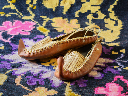 Opanci, traditional handcrafted leather folk shoes, a part of the Serbian national costume, are lying on a kilim, a traditional handmade flat-woven floor rug. Selective focus.