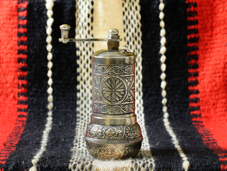 Turkish vintage hand spice grinder, alternatively called pepper mill, on an old hand-woven fabric.