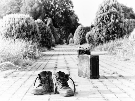 Old ankle leather boots in a foreground, in the middle of a brick road. A film camera on an antique cardboard suitcase with corner protectors, in a blurry background. A black-and-white photo effect.