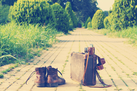 Shabby ankle boots next to a vintage cardboard suitcase, a film camera in its open leather case, and a yellow brick road, grass, and trees in a blurry background. Post-processed. Фото со стока