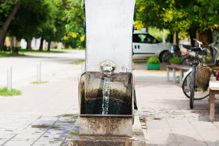 Flowing artesian well, and a decorative spigot installed on it. Selective focus. The blurry contours of a vintage bicycle with a wicker bag is visible in the nearest surroundings.