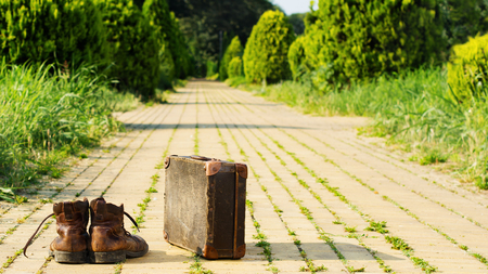 It's time to wander the earth. Shabby boots and a vintage suitcase in the middle of a yellow brick road. Sixteen-by-Nine crop.