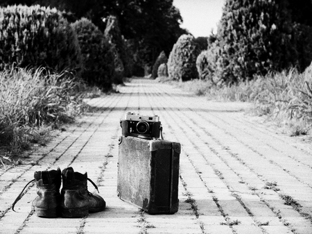 Leather ankle boots, a vintage cardboard suitcase, and a film camera in its open leather case, in the middle of a brick road. A black-and-white photo effect. Grain noise added.