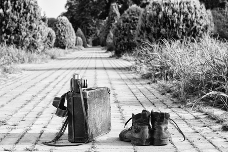 Traveling light! Worn ankle boots next to a vintage cardboard suitcase, a film camera in its open leather case, and a brick road. A black-and-white photo effect.