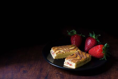 Sponge cakes with strawberry syrup filling, decorated with cocoa topping, and served with fresh strawberries, on a black plate, and a rustic wood plank background. There is a lot of copy space beside.