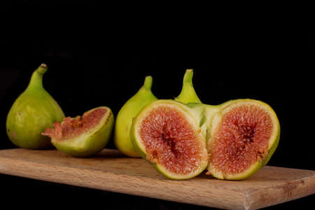 Ripe fresh figs are lying on a wooden cutting board. Two halves of a common fig syconium are lying in the front plane, showing its one-seeded fruits. A few figs stacked in a blurry background.