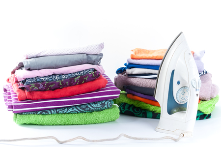 electric material: Ironing. Stack of clothing and iron on a white background
