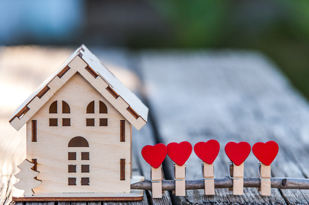 A toy house with a fence of hearts. A symbol of a house where love reigns. Theme of happiness, warmth, good luck, love, construction, travel, hotel business, family