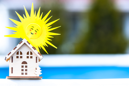 Toy house with a sun on a beautiful background. Symbol of happiness, family and peace