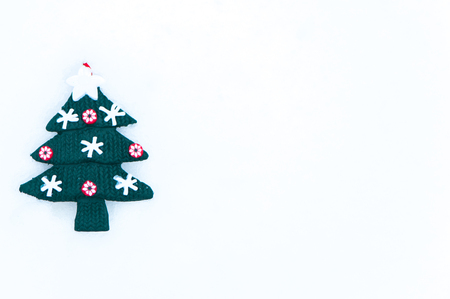 souvenir Decorated Christmas tree in the snow, a symbol of the new year. Space for text. Christmas, New Year congratulations.