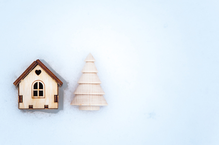 Toy house with a Christmas tree in the snow., a deer space for text. Christmas, New Year congratulations.   写真素材