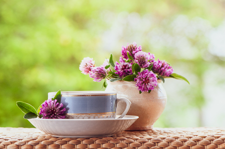 Ð'eautiful summer composition of a cup of tea and clover flowers on a natural green background, a concept of good morning, summer mood, happiness 免版税图像