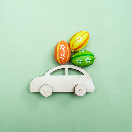 Easter theme. Car with Easter eggs on a green monophonic background. Minimalism, top view, flat.