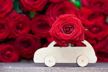 Konzept Valentinstag, Liebe, Maschine transportiert eine Blume auf dem Hintergrund von roten Rosen. Stilvolles Liebeskonzept, Platz für Text. Standard-Bild