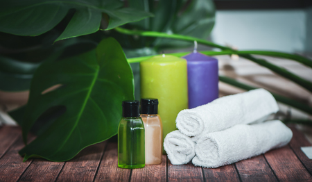 Spa concept, aloe gels and oils, candles and towels on natural wooden background