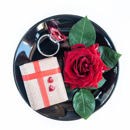 Proposal to marry, wedding concept. Valentines Day, lovers, Rose and a ring on a dish Фото со стока