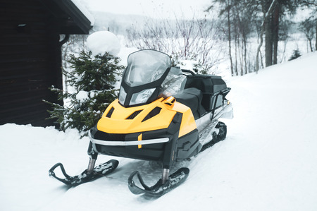 Snowmobile, empty, against the backdrop of the winter forest