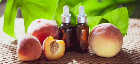Bottles with peach oil, fresh peach fruit whole and half on a natural tropical background. Homeopathic and herbal medicine.