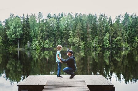 Father with a small daughter are standing on the pier of a beautiful lake, they are talking sweetly. Father and daughter relationship concept, fathers day. Family love