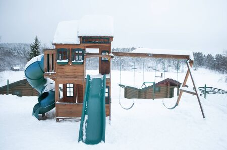 Children's game system, slide swings and houses on the background of a winter park Zdjęcie Seryjne