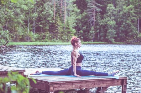 Young yogi  girl  practicing yoga, stretching in Monkey God exercise, Splits, Hanumanasana pose on the lake. The concept of appeasement,  healthy lifestyle. Stock Photo