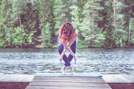 Yoga meditation  by Young yogi  girl  on the pier of a beautiful lake.  Concept of healthy life and natural balance Stock Photo