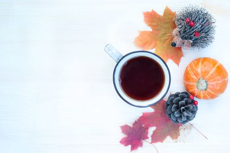 Background on the theme of autumn. Cozy background with maple leaves, pumpkins and a cup of tea with copy space. Top view, flat lay