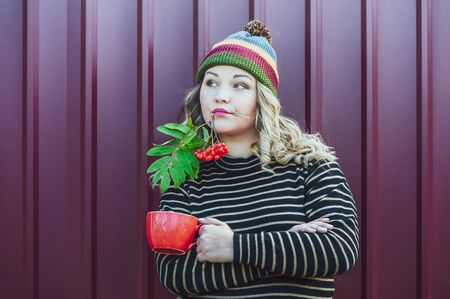 Expressive girl in a juicy autumn hat with a branch of mountain ash in her mouth and a cup of tea in her hand. Theme of autumn, bright colors and beauty. Bright photo of a beautiful girl in an autumn hat and a sweater on a stylish background