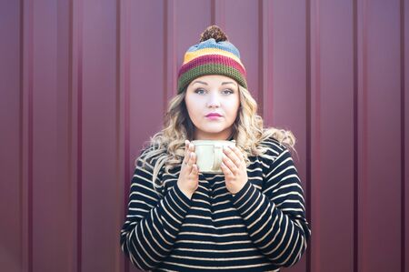 Expressive girl in a juicy autumn hat with cup of tea in her hand. Theme of autumn, bright colors and beauty. Bright photo of a beautiful girl in an autumn hat and a sweater on a stylish background