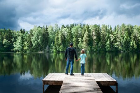 Father with a small daughter are standing on the pier of a beautiful lake, the father is opening a new world for his daughter. Father and daughter relationship concept
