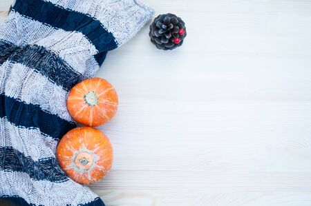 Background on the theme of autumn. Cozy background with a sweater and pumpkins  with copy space. Top view, flat lay