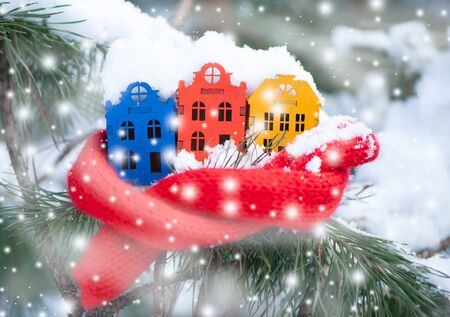 Toy houses is wrapped in a warm scarf, its snowing on a natural natural background of a real fir in the snow, toned. Concept of winter, Christmas, new year,  warm, cozy in the city