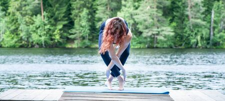 Young girl practicing yoga in the nature on the lake. Female happiness. Concept of healthy life and natural balance. Landscape background, space for text