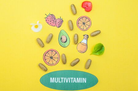 Concept multivitamins and supplements, a fountain of their capsules and useful products on a yellow background Imagens
