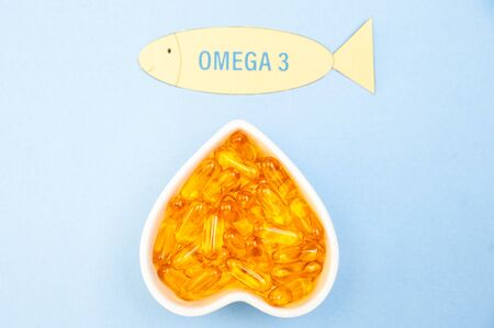 Heart-shape plate with fish oil capsules omega 3, healthy product   and   supplement  concept close up,  flat lay