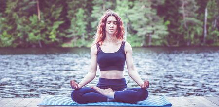 Beautiful girl in a yoga pose on the lake. Lotus position ,  Padmasana. The concept of appeasement,  healthy lifestyle. Panoramic view
