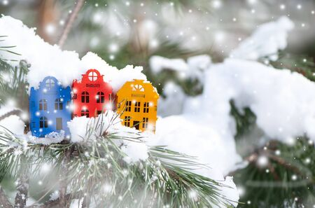 Toy houses  on a natural natural background of a real fir in the snow. Concept of winter, Christmas, new year,  warm, cozy in the city. Space for text